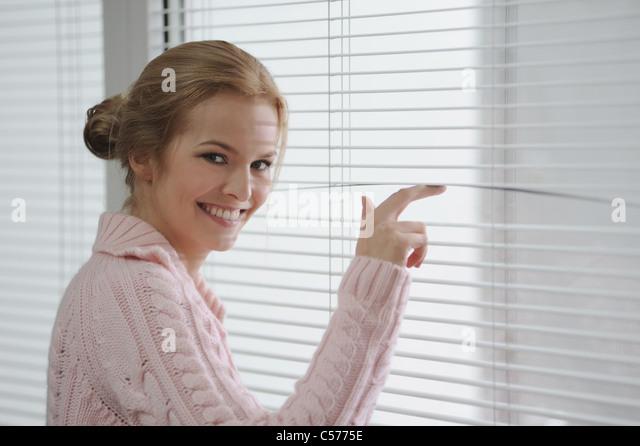 Lächelnde Frau, die durch Jalousien Stockbild