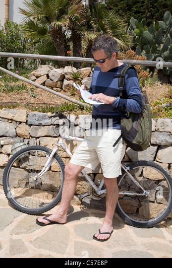 Biker, die Karte auf der Straße lesen Stockbild