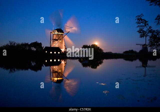 Den Niederlanden, Kinderdijk, beleuchtete Windmühle, UNESCO-Weltkulturerbe. Mondaufgang. Stockbild