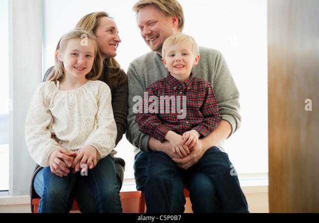 Familie sitzt auf der Fensterbank, Porträt Stockbild