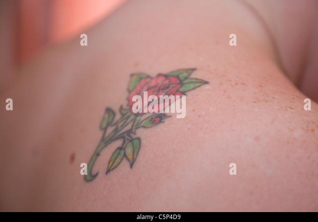 Rose tattoo auf der Schulter der Braut, bevor sie auf ihr Brautkleid legt Stockbild