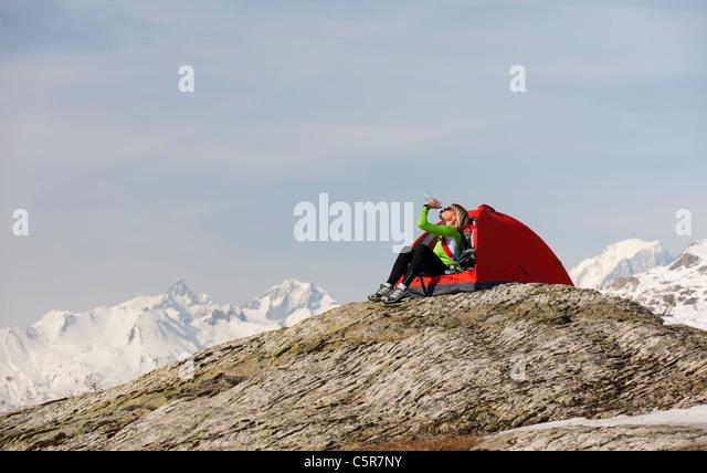 Eine Frau, die im verschneiten Hochgebirge Flüssigkeit trinken camping Re-Hydrat. Stockbild