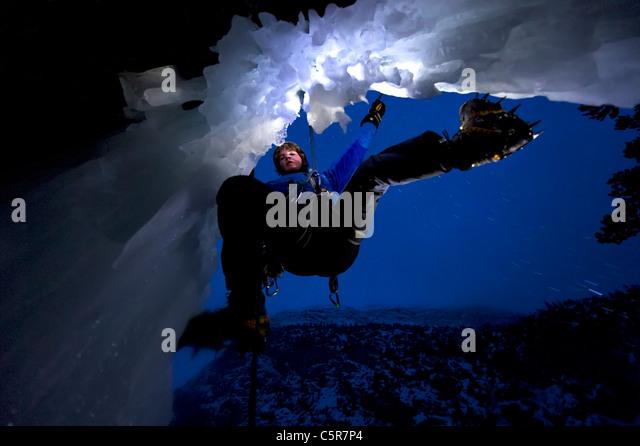 Eis-klettern in der Nacht am Rande einer Höhle. Stockbild