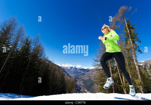 Eine Frau, Joggen in verschneiten Bergen. Stockbild