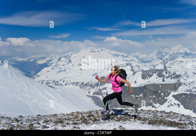 Eine Frau läuft schnell über schneebedeckte Berge. Stockbild