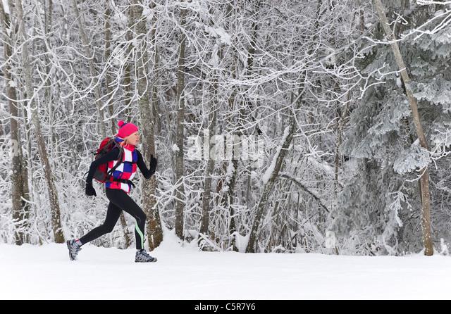 Ein Jogger läuft durch einen frostigen Wald. Stockbild