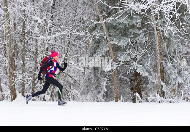 Jogger laufen durch einen verschneiten Winterwald. Stockbild