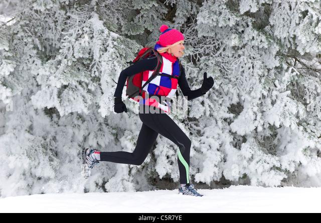 Ein Jogger entlang einem verschneiten Kiefernwald. Stockbild