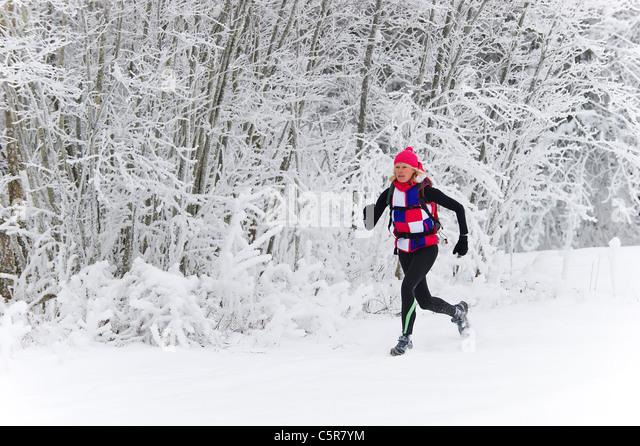 Joggen durch den Schnee bedeckt Wald. Stockbild
