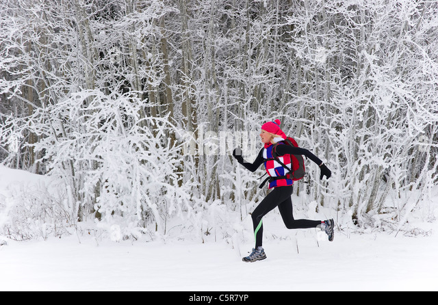Ein Jogger läuft schnell durch einen Winterwald. Stockbild