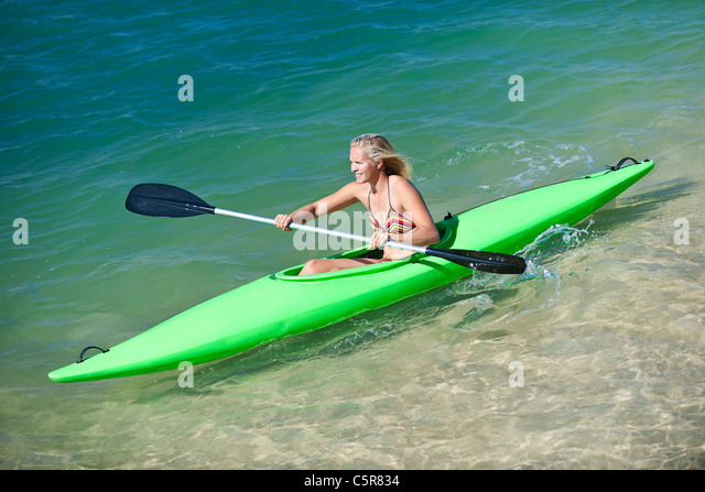 Eine Frau paddelt ihr Kanu an einem sonnigen Tag. Stockbild