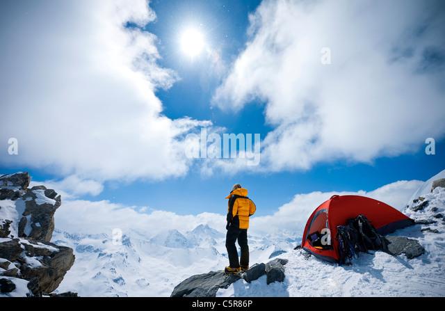 Ein Bergsteiger blickt auf schneebedeckten Berge. Stockbild