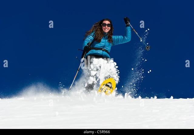 Eine Frau, die Spaß haben einen tiefen Neuschnee-Feld unten Schneeschuhwandern. Stockbild