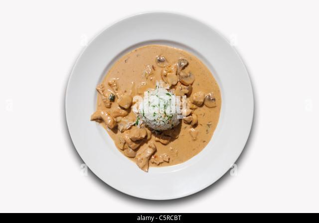 Nahaufnahme von Putenfleisch mit Champignons und gekochtem Reis vor weißem Hintergrund Stockbild