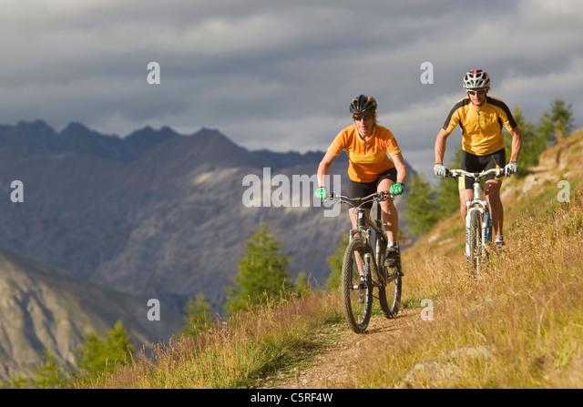 Italien, Livigno, Ansicht von Mann und Frau Reiten Mountainbike Stockbild