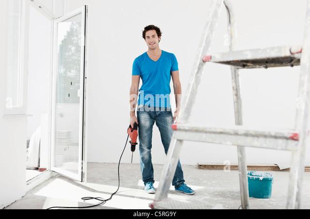 Deutschland, Köln, junger Mann mit elektrischen Bohrer in die Renovierung der Wohnung Stockbild