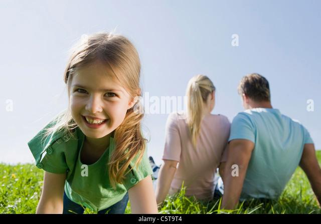 Deutschland, Bayern, München, Familie sitzt auf Wiese, Mädchen (6-7) im Vordergrund, Lächeln, Porträt Stockbild