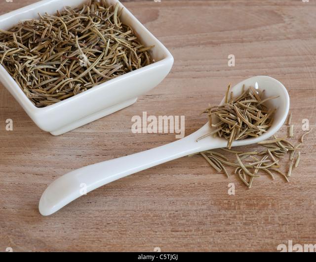Einem Löffel und einer Dishful von aromatischem Rosmarinblätter getrocknet bis auf eine hölzerne Stockbild