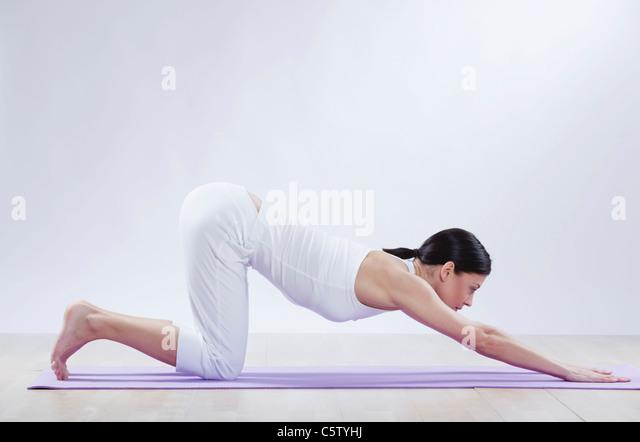 Mitte Erwachsene Frau beim Yoga vor weißem Hintergrund Stockbild