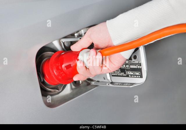 Hand der Frau hält Hochspannungskabel laden Elektro-Auto, Nahaufnahme Stockbild