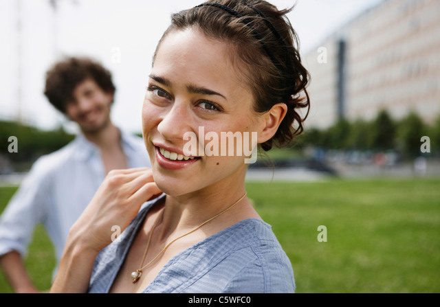 Deutschland, Berlin, junge Frau, Mann im Hintergrund, Porträt, Nahaufnahme Stockbild