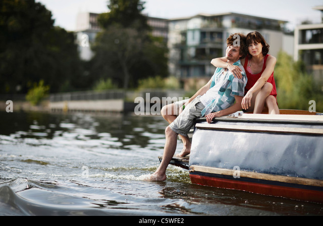 Deutschland, Berlin, junges Paar sitzt auf Motorboot, Porträt Stockbild