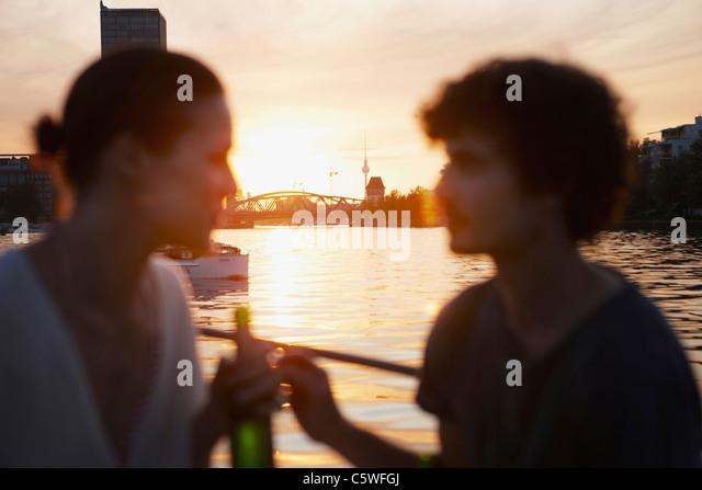 Deutschland, Berlin, junges Paar auf Boot, holding, Flaschen, Seitenansicht, portrait Stockbild