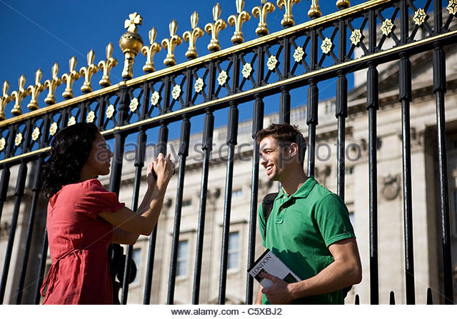 Eine junge Frau, die ein Bild von ihrem Freund vor Buckingham Palace Stockbild