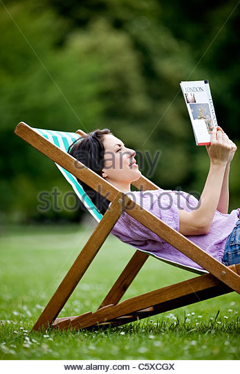 Eine junge Frau sitzt auf einem Liegestuhl im St James Park, Blick auf einen Reiseführer Stockbild