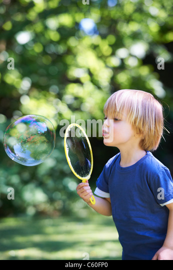 Junge übergroße Seifenblase im Hinterhof Stockbild