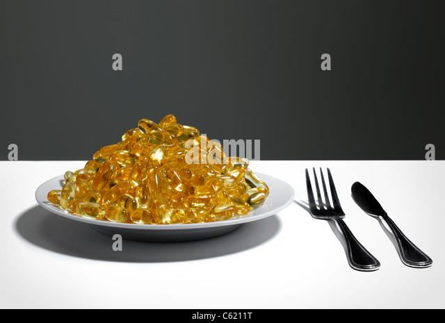 Teller voller Vitamin E oder Fisch-Öl-Kapseln Stockbild