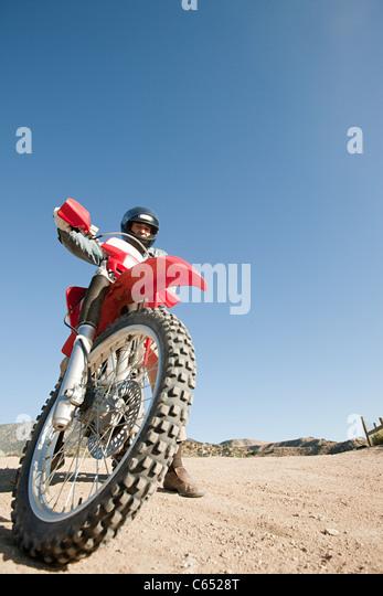 Mann reitet Schmutzfahrrad auf Feldweg Stockbild