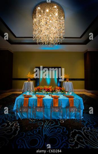 Bild von einem Banketttisch mit blauen Stoffen und rot und orange Blumen-arrangements Stockbild