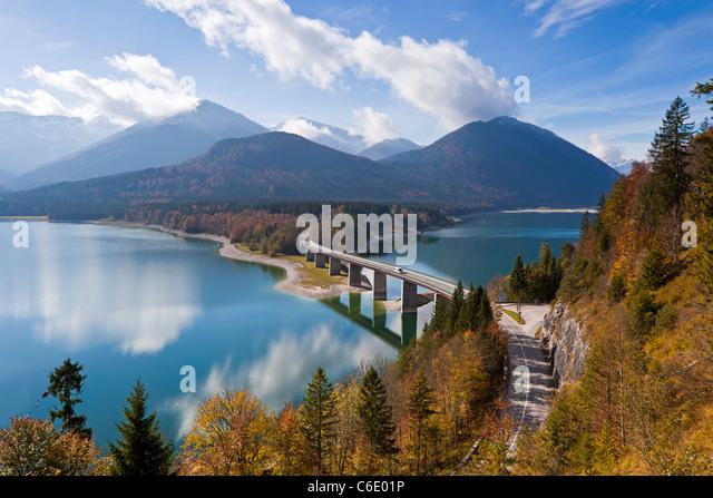 Reflexionen einer Straße Brücke über See Sylvensteinspeicher, mit Bergen im Hintergrund, in Bayern, Stockbild