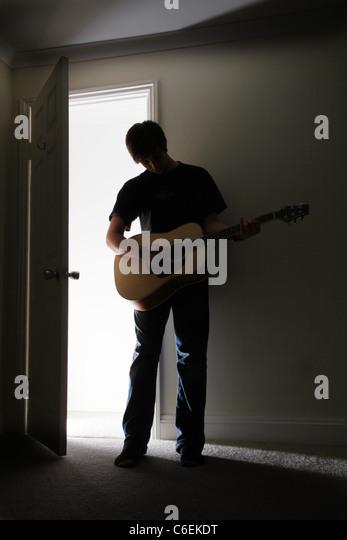 Junger Mann stehend in einem dunklen Raum eine akustische Gitarre zu spielen. Stockbild
