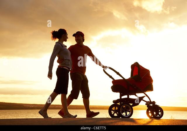 Silhouetten von glücklichen Eltern mit Kinderwagen zu Fuß an der Küste Stockbild