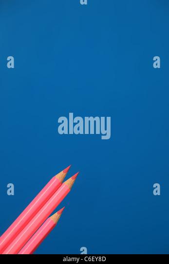Drei Rosa Buntstifte und Bleistifte, zwei lange man kurze. Stockbild