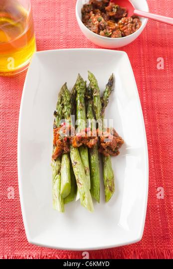 Spargel mit getrockneten Tomaten und Paprika Stockbild
