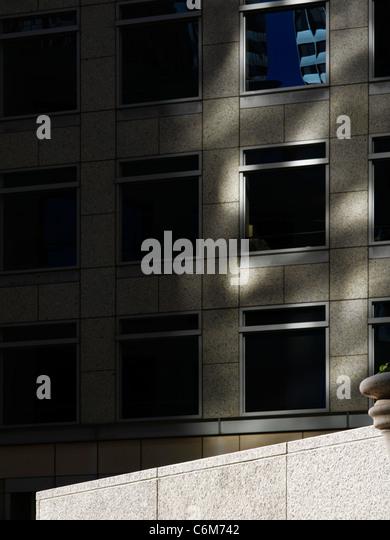 Detail der leeren Bürogebäude Plaza mit steinernen Sims bei strahlendem Sonnenschein gesehen drastisch Stockbild