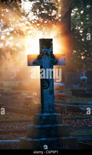 Friedhofskreuz Grabsteine leuchtet bis in den frühen Morgen Sonnenlicht durch Nebel. England Stockbild