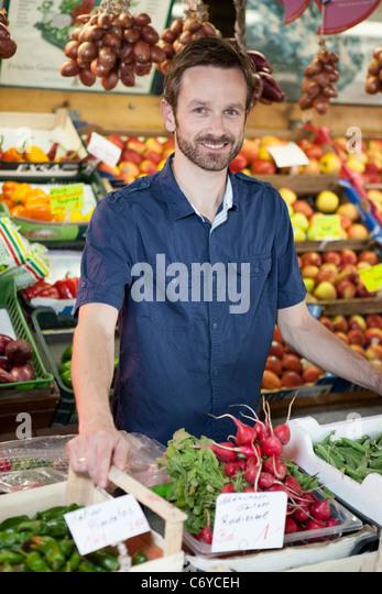 Mann lächelnd in Produkten stand Stockbild