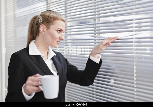 Geschäftsfrau aus Jalousien peering Stockbild