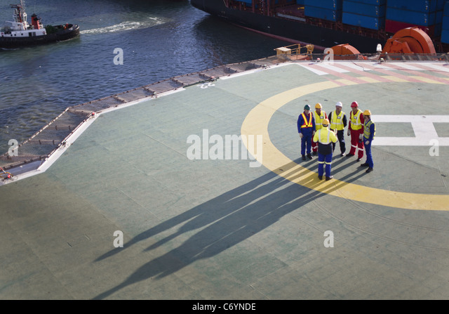 Arbeiter am Hubschrauberlandeplatz der Bohrinsel sprechen Stockbild