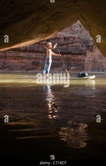 Frau auf Paddel Board vor Höhle beim rafting auf der unteren San Juan River, Mexican Hat, Colorado. Stockbild