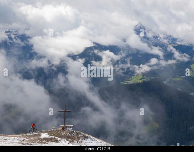 Ein Mountainbiker kommt an ein Kreuz auf dem Gipfel des Kronplatz, Berge und Wolken im Hintergrund. Stockbild