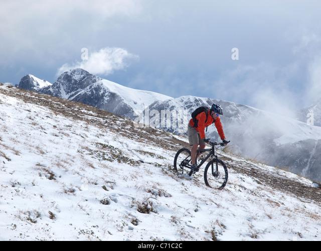Ein Mountainbiker fährt durch den Schnee am Kronplatz, Berge und Wolken im Hintergrund. Stockbild