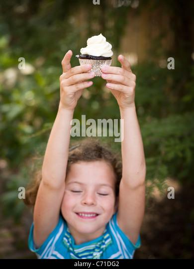 Mädchen Posen mit cupcake Stockbild