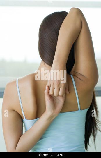 Frau tut Yoga-Kuh-Gesicht-Pose, Rückansicht Stockbild