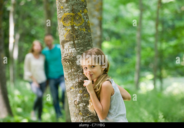 Mädchen versteckt sich hinter Baum mit Finger auf die Lippen Stockbild