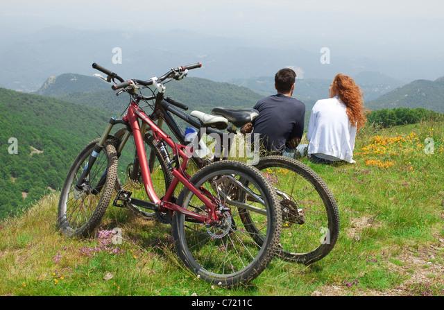 Paar Zusammensitzen auf Hügel, hinter ihnen Fahrräder geparkt betrachten, Stockbild